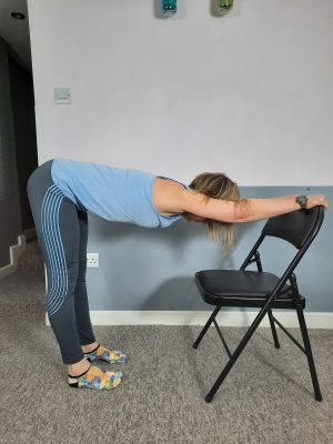Author doing a back stretch via a hip hinge shape, hands supported on a chair