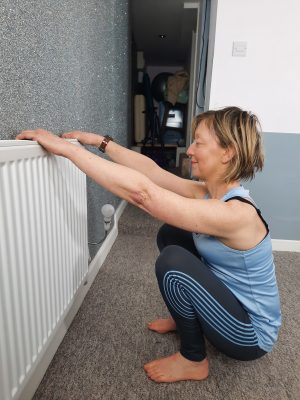 deep squat assisted by holding a radiator